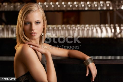 An attractive and classy young woman standing at the bar of a upper class establishment