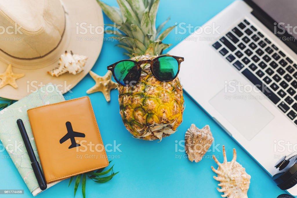 スタイリッシュなノート パソコン、パスポート、サングラス、地図、帽子、ヘッドフォン、シェル、トレンディな青紙ノートブック パイナップル。フラット横たわっていた。夏の休暇の概� ストックフォト