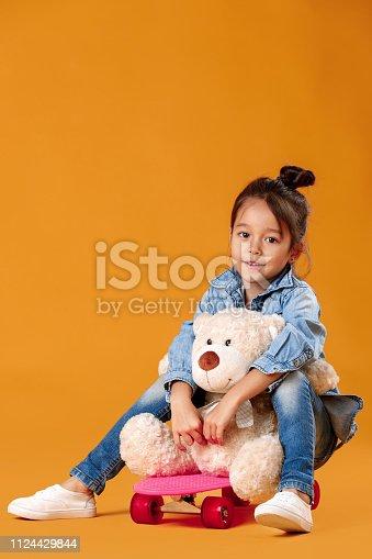 istock Stylish little child girl with skateboard in denim on orange background 1124429844