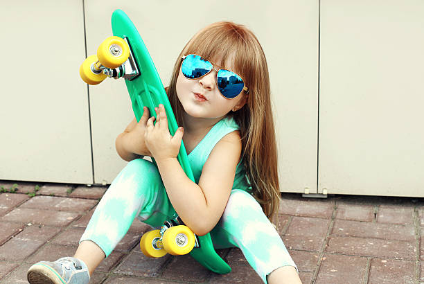 stylish little girl child wearing sunglasses with skateboard in city stock photo