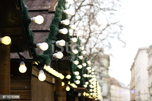 istock stylish luxury christmas garland lights and wreaths on wwooden cabins, celebration decoration for holidays in the city 971075398