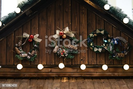 istock stylish luxury christmas garland lights and wreaths on wwooden cabins, celebration decoration for holidays in the city 971082420