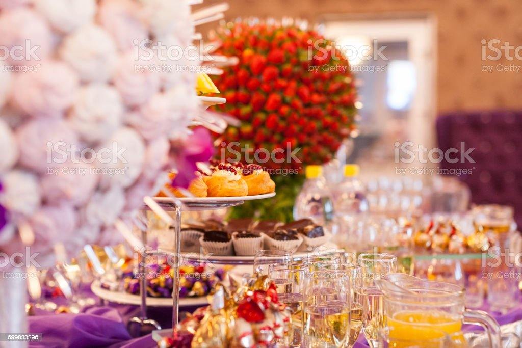 stylish luxury decorated candy bar for the celebration of a wedding of happy couple, cathering in the restaurant, Sweet holiday buffet with cupcakes and other desserts. stock photo