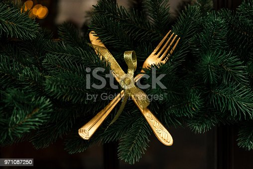 istock stylish luxury  golden knife and fork on christmas wreath, creative celebration decoration for holidays in the city 971087250