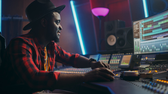 Stylish Male Audio Engineer Working in Music Recording Studio, Uses Mixing Board, Software to Create Modern Hit Song. Creative Artist Musician Working on Workdesk Control Surface to Produce New Song