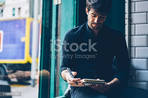 1174436608 istock photo Stylish male entrepreneur dressed in black shirt reading notepad with notes for developing own business plan.Pensive young man thinking on writing creative ideas in notebook sitting in coworking space 1168817221