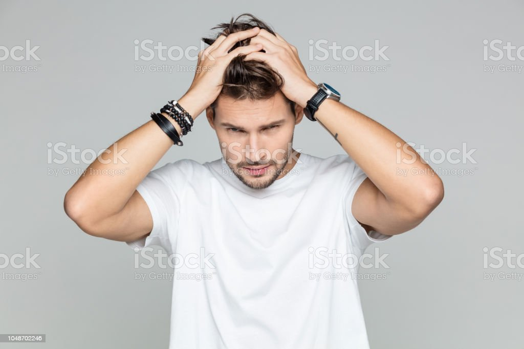 Stylish male model posing Portrait of attractive young man posing with hands in hair on grey background 25-29 Years Stock Photo