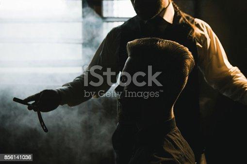 istock Stylish male shaving with dangerous sharp razor 856141036