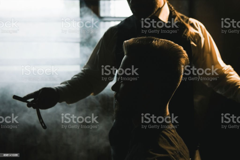 Stylish male shaving with dangerous sharp razor stock photo
