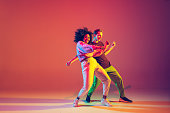 istock Stylish man and woman dancing hip-hop in bright clothes on gradient background at dance hall in neon light 1267332085