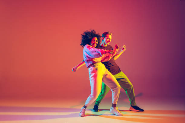 Stylish man and woman dancing hip-hop in bright clothes on gradient background at dance hall in neon light stock photo