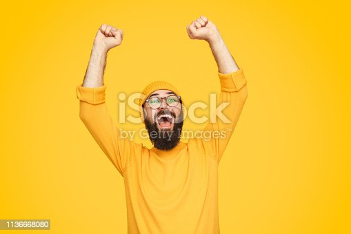 Handsome bearded guy in bright outfit raising hands and screaming while celebrating victory on yellow background
