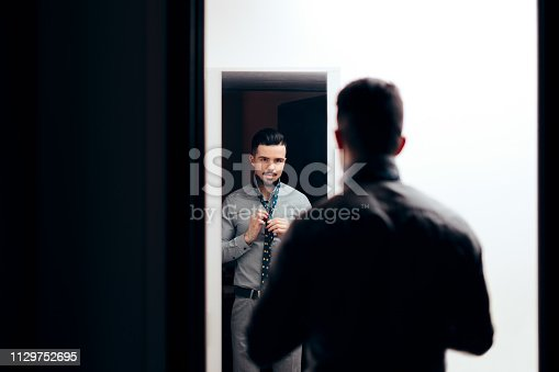 istock Stylish  Man Checking Himself in the Mirror Trying on Clothes 1129752695