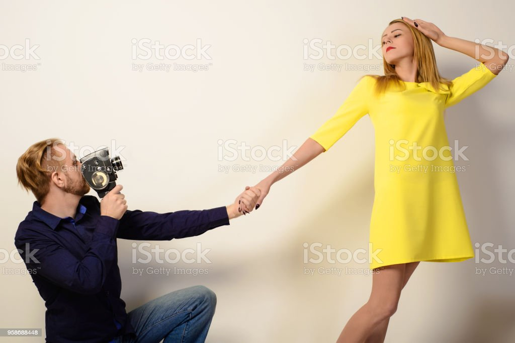Stylish man in a blue shirt is filming a slim woman in a yellow dress stock photo