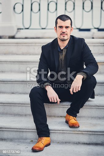 istock A stylish man in a jacket, shirt, trousers and brown leather shoes sits on concrete steps. Portrait of a macho sitting on the street on a concrete staircase in a stylish suit and quality shoes. 931273740
