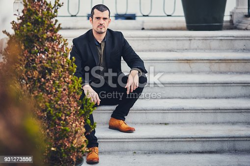 istock A stylish man in a jacket, shirt, trousers and brown leather shoes sits on concrete steps. Portrait of a macho sitting on the street on a concrete staircase in a stylish suit and quality shoes. 931273886