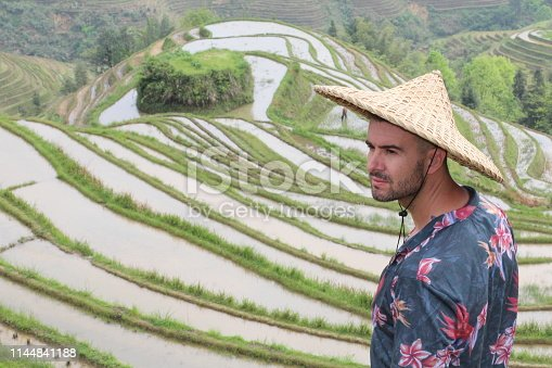 istock Stylish man in Asian rice terraces 1144841188