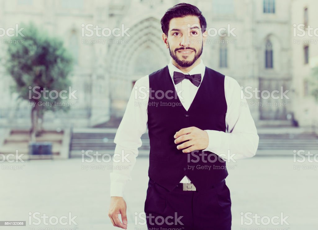 Stylish man in bow tie against cathedral royalty-free stock photo