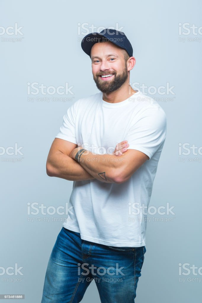 Stylish man in studio Portrait of stylish man is casual wear standing on white background with arms crossed Adult Stock Photo