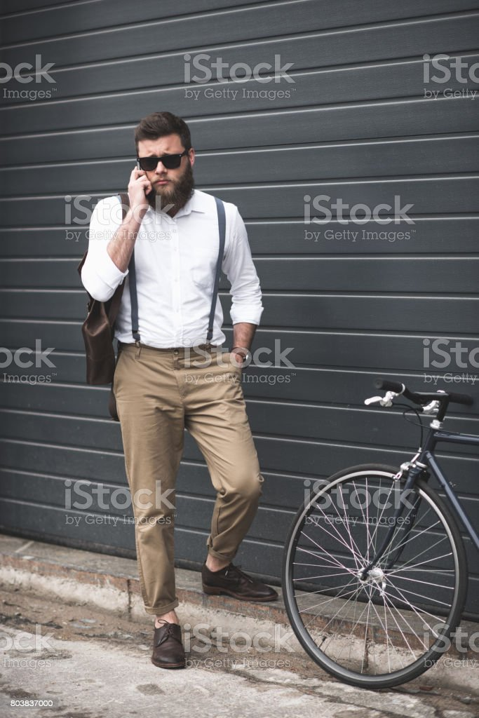 stylish man in sunglasses and suspenders using smartphone and standing near bike stock photo