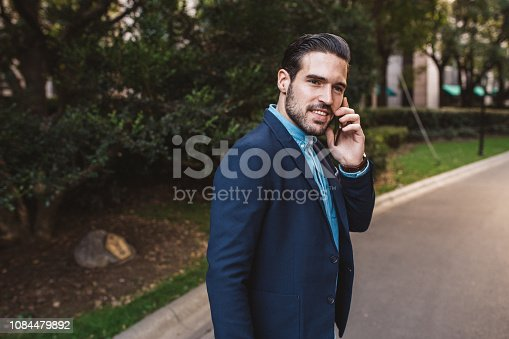 One young modern man talking on phone in the park