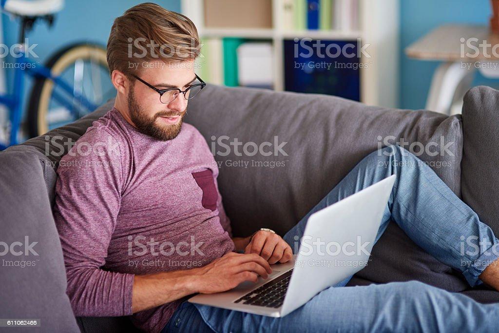 Stylish man using laptop at home stock photo