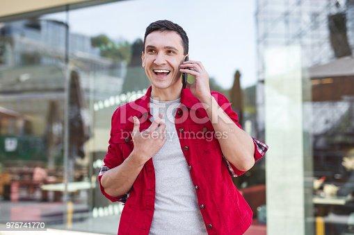 istock Stylish man wearing red jacket speaking on the phone 975741770