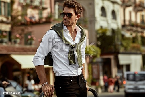 Stylish man wearing sunglasses and white shirt with tied sweater on shoulders