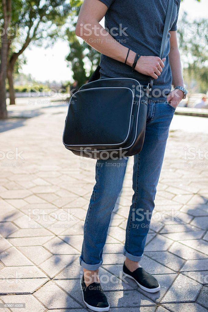 Stylish man with a bag posing in city park stock photo
