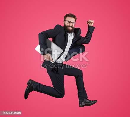 istock Stylish man with laptop running fast 1094061938