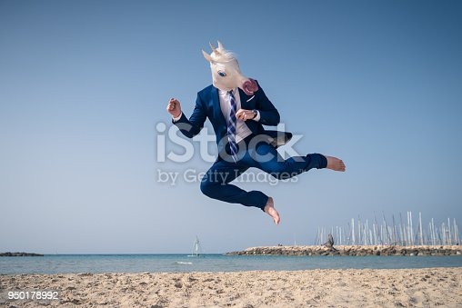 Stylish manager in funny mask and elegant suit jumps on beach. Serious fighter strikes in flight. Unicorn on background of sea and sky