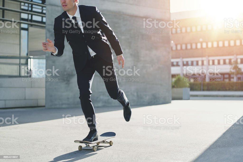 Stylish manager riding a skateboard in city – zdjęcie