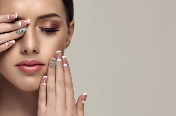 Stylish manicure and make up in a pale-pink color. Young appealing woman is showing pale-pink french style manicure with  rhinestone on the slender fingers. Perfect makeup and trendy manicure. stage make up stock pictures, royalty-free photos & images