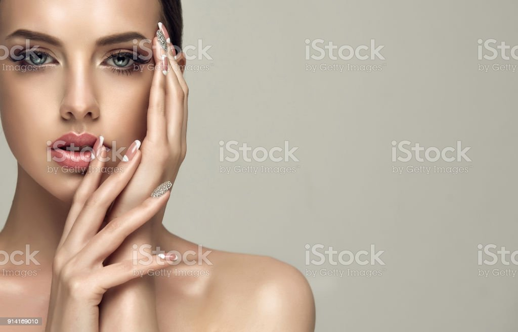 Stylish manicure and make up in a pale-pink color. stock photo