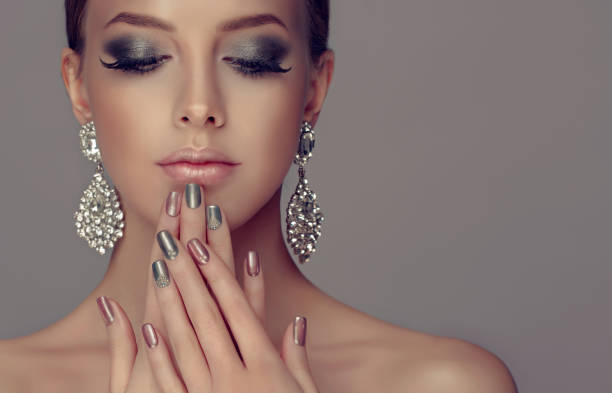 Stylish manicure and make up in a silver color. Beautiful woman-model dressed in a big silver earings is showing silver and rose manicure on the nails and rose lipstick on the lips. Fashion makeup and cosmetic. stage make up stock pictures, royalty-free photos & images