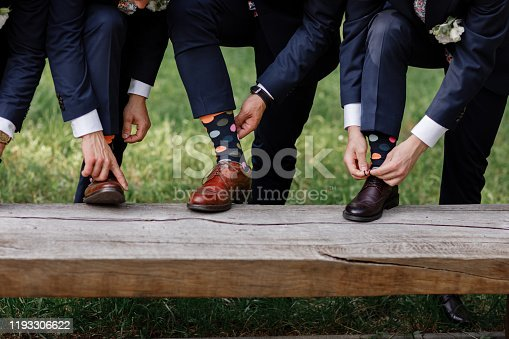 stylish men's socks. Stylish suitcase, men's legs, multicolored socks and new shoes. Concept of style, fashion, beauty and vacation.