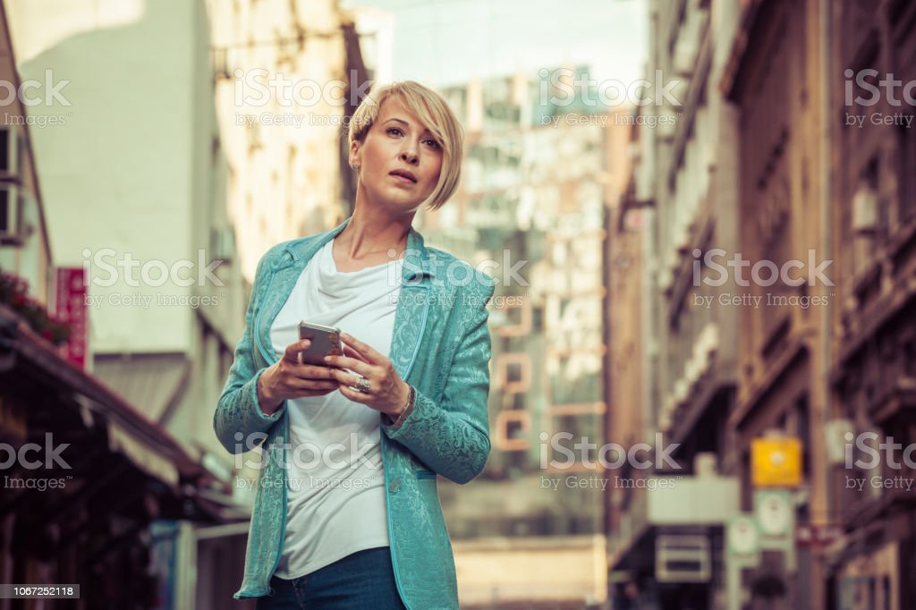 Stylish mid-age business woman texting on the street stock photo