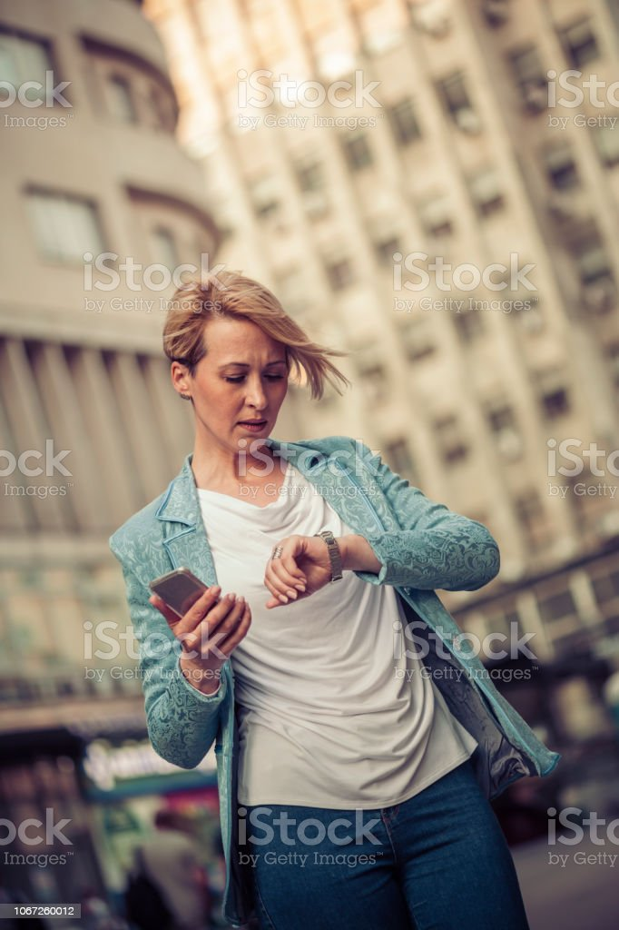 Stylish mid-age woman waiting for someone in the street stock photo