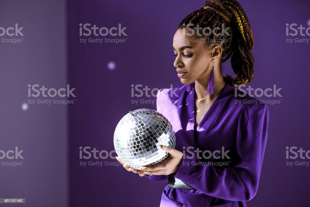 stylish mulatto model posing in purple jacket with disco ball, ultra...