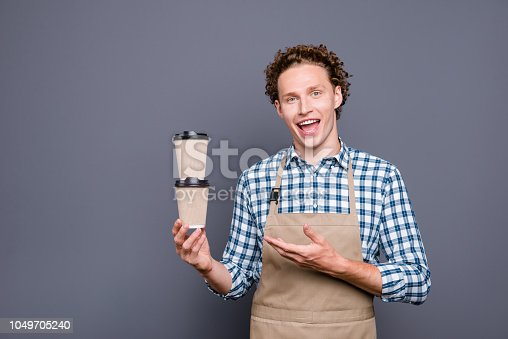 istock Stylish nice attractive cheerful guy with wavy hair in casual checkered shirt and apron, holding, showing two paper cups pyramid, offering take-away, rest, pause, relax. Isolated over grey background 1049705240