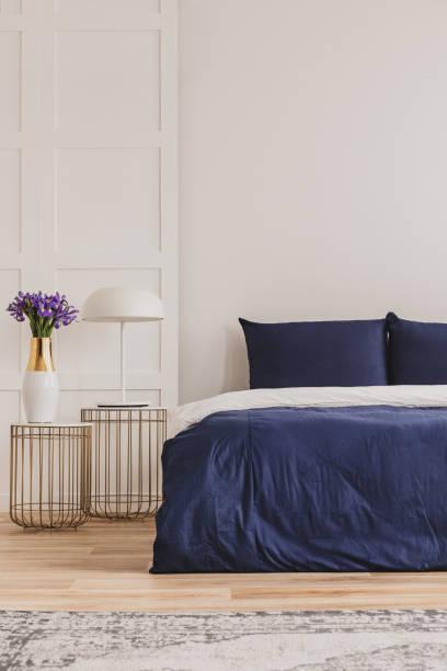 stilvoller nachttisch mit industrielampe und trendigem nachttisch mit blumen in vase neben einfachen marineblauen bett - marineblau schlafzimmer stock-fotos und bilder