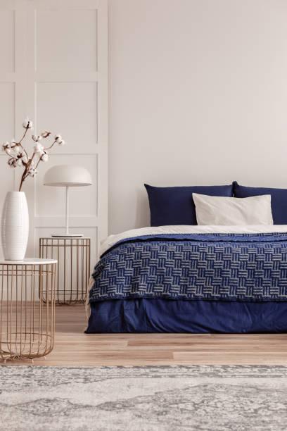 stilvoller nachttisch mit weißer industrielampe und trendigem nachttisch mit baumwollblumen in vase im noblen schlafzimmer-interieur - marineblau schlafzimmer stock-fotos und bilder