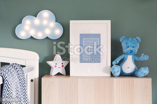 istock Stylish nursery interior with mock up photo frame, teddy bear, star and blue cloud. Green background wall. 979584762