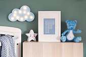 Stylish nursery interior with mock up photo frame, teddy bear, star and blue cloud. Green background wall.