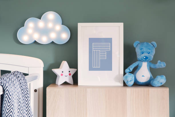 Stylish nursery interior with mock up photo frame, teddy bear, star and blue cloud. Green background wall. stock photo