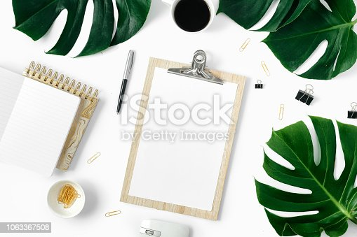 Stylish office table desk. Modern female workspace with monstera leaves, clipboard and accessories flat lay, top view