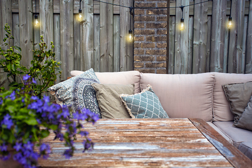 Stylish outdoor garden furniture, sofa with cushions and lamps, light bulbs hanging, cozy modern corner on terrace