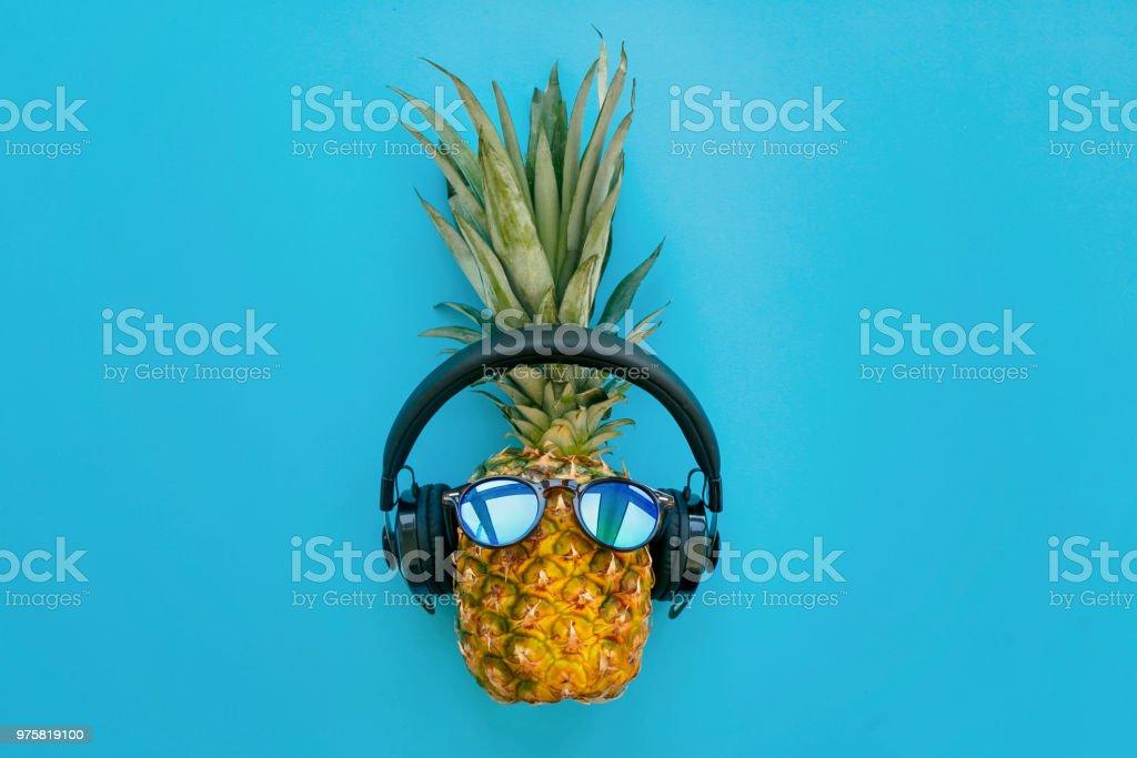 stilvolle Ananas mit Sonnenbrille und Kopfhörer auf trendiges blaues Papierhintergrund. Sommer flach zu legen. Urlaub und Party-Konzept. Platz für Text. Hipster-Urlaub - Lizenzfrei Ananas Stock-Foto