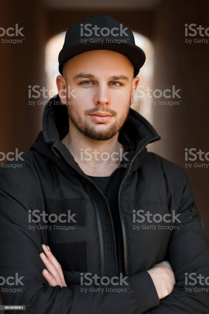 1d3199d9c74 Stylish portrait of a young handsome man in a black baseball cap with a black  winter jacket on the street - Stock image .
