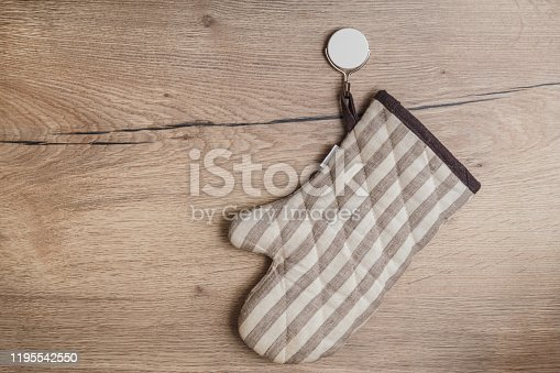 839034546 istock photo Stylish pot-holder hanging on a hook on wooden wall in kitchen. Sticking hook 1195542550